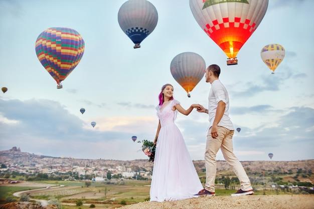 Влюбленная пара стоит на фоне воздушных шаров Premium Фотографии