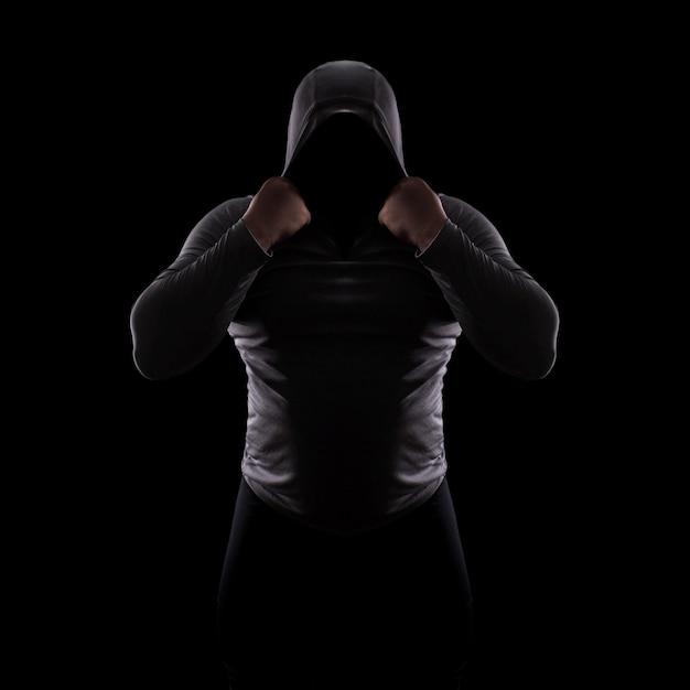 顔のないフードでシルエット男性の戦いクラブ Premium写真
