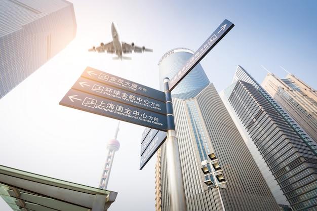 中国の上海で夕暮れ時に旅客機が付いている近代的な建物。 Premium写真