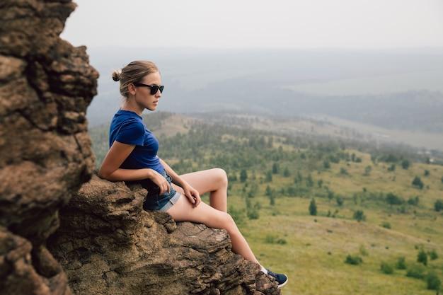 若い美しいブロンドの観光客の女の子は岩の岩の棚の上に座って、霧の早朝に遠くに見えます。 Premium写真