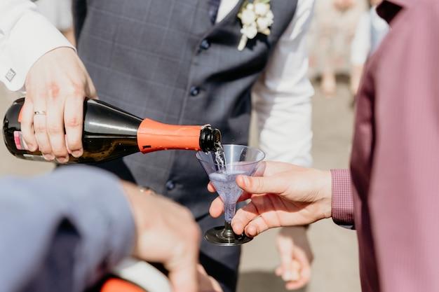 新郎は、ゲストをクローズアップするためにシャンパンをプラスチックガラスに注ぎます。 Premium写真