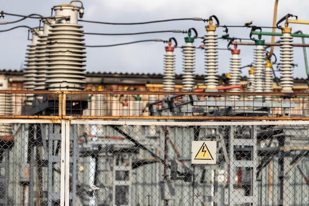 送電線の変電所を囲むメッシュフェンスには、高電圧の危険性に関する警告が表示されています。 Premium写真