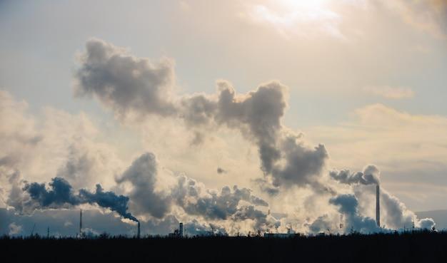工場の煙突は、濃い煙で大気を汚染します。 Premium写真