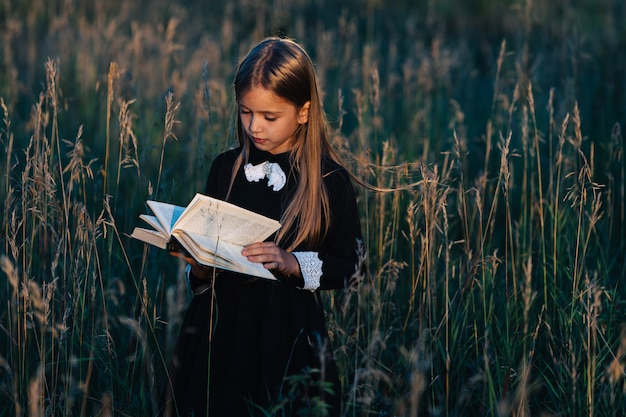 黒いドレスを着た少女が背の高い草の中に立って、夕日に照らして緑の本を読みます。 Premium写真
