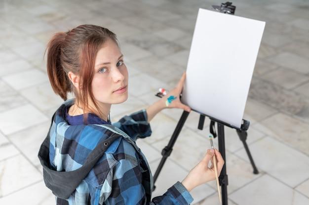 Молодой подросток женщина художник с кистью в руках готовится к живописи маслом. белый холст с копией пространства расположен на черном мольберте. Premium Фотографии