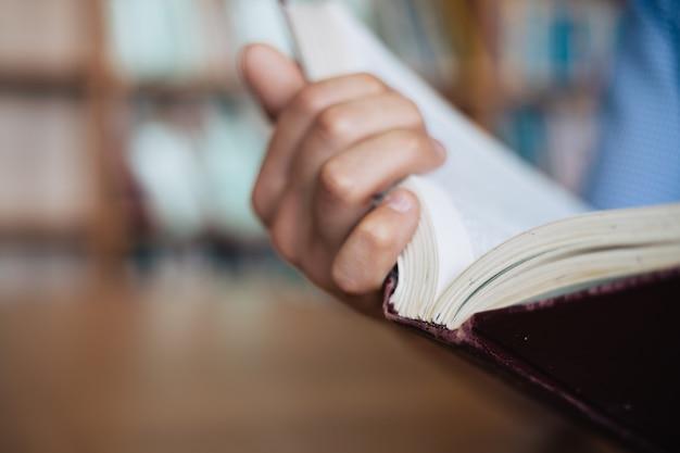 男性の手は開いた本を保持しています。本の背面のクローズアップのビュー。 Premium写真