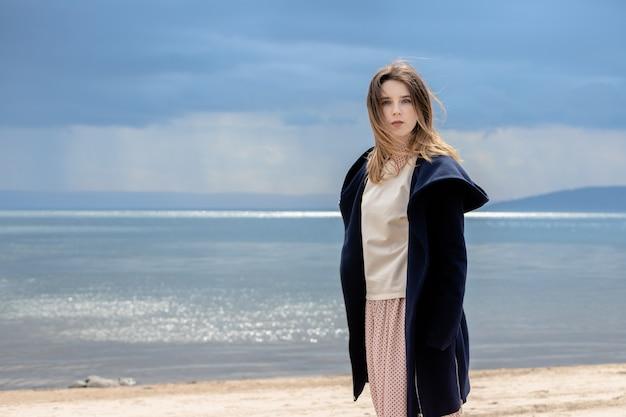 大人の美しい少女が、雨が近づいてくる雲を背景に海岸に立っています。 Premium写真