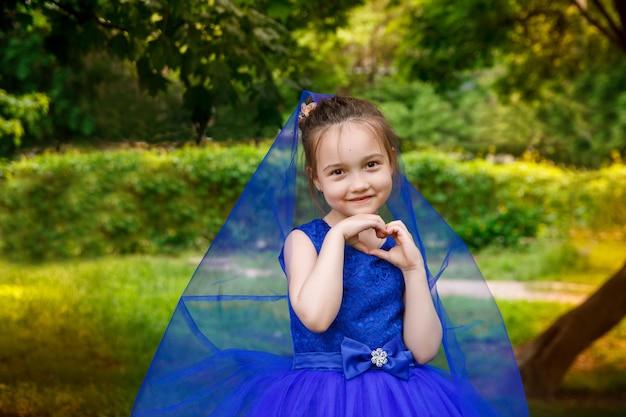 公園で青い誕生日ドレスの少女。笑顔の子供屋外 Premium写真