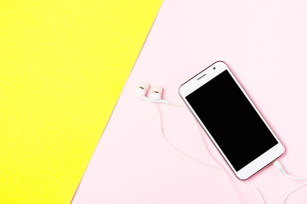 Смартфон с наушниками на желтом и розовом фоне Premium Фотографии