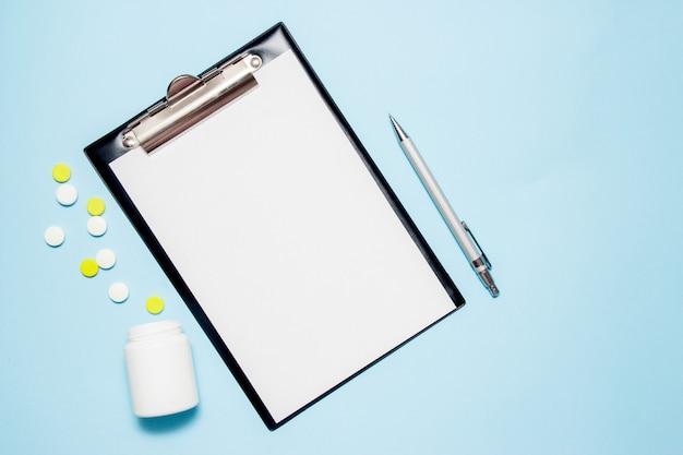 医者の処方を書くための空白の紙の平面図です。青の丸薬 Premium写真