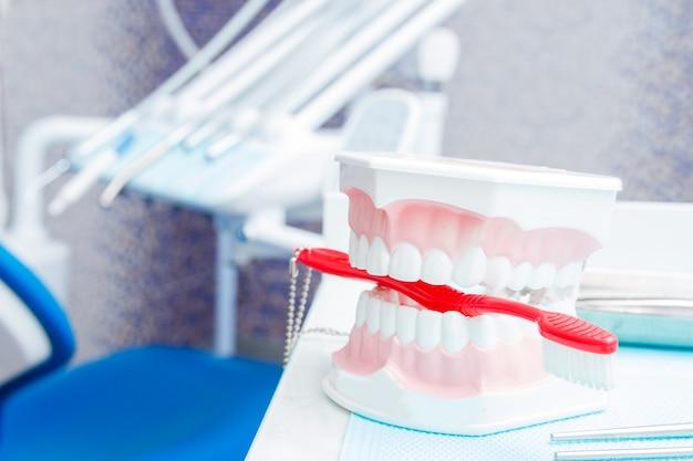 白い歯のダミーと歯科医院の器具。 Premium写真