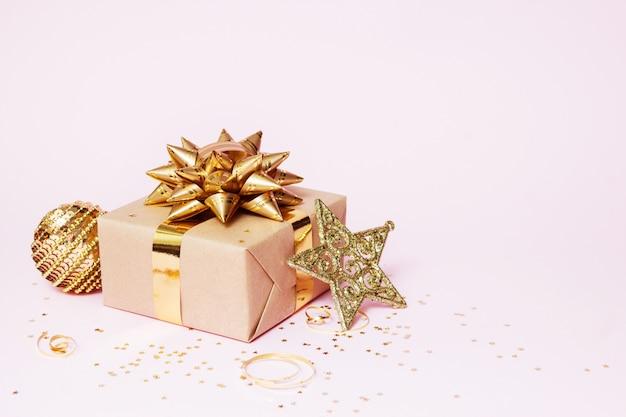 Рождественская открытка композиция. подарок из крафт-бумаги с золотым шаром, звездой конфетти и золотым декором на розовом фоне Premium Фотографии