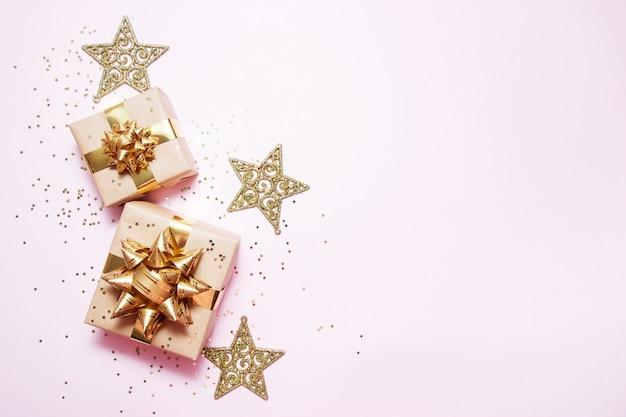 クリスマスのグリーティングカードの構成。ゴールデンボール、紙吹雪星、ピンクの背景の金の装飾とクラフトペーパーギフト Premium写真