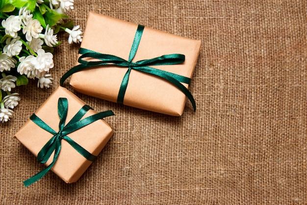 Подарки в крафт-бумагу с белыми цветами, лежа на вретище. Premium Фотографии