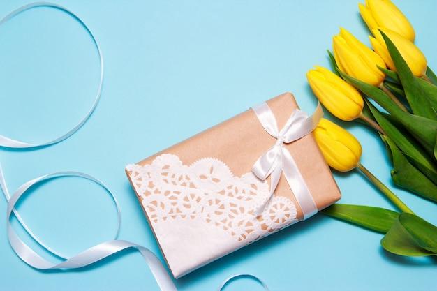 黄色いチューリップの花束とペーパークラフトの贈り物は、青い紙の背景にレースナプキンで飾られています。 Premium写真