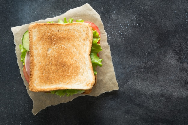 Бутерброд с беконом, помидор, лук, салат на черном Premium Фотографии