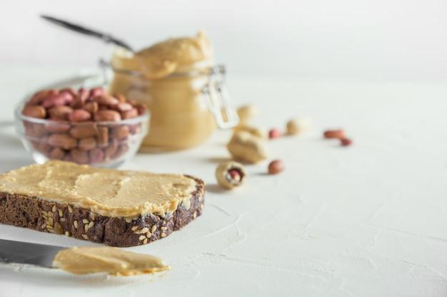 茶色の全粒粉パンにピーナッツペースト。健康的な栄養。 Premium写真