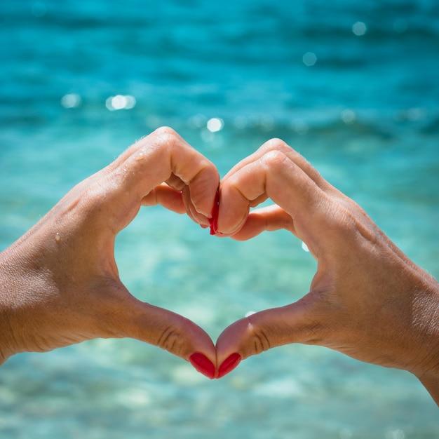 Женская рука с красным ногтем в форме сердца на фоне моря. концепция любви Premium Фотографии