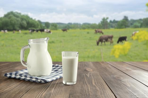 暗い木製のテーブルと草原の牛とぼやけた風景のガラスの新鮮な牛乳。健康的な食事。素朴なスタイル。 Premium写真