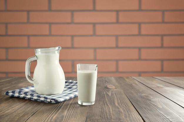 新鮮な牛乳と木製のテーブルの上の水差しのガラスは、モンタージュ製品の背景としてキッチンをぼかします。 Premium写真