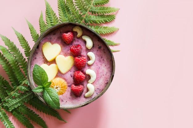 ピンクのココナッツボウルにフルーツで飾られた健康的な朝食バナナとブルーベリーのスムージー。 Premium写真