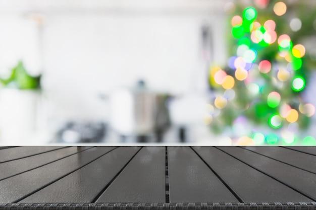 卓上にクリスマスツリーとぼやけキッチン。製品を表示するための背景。 Premium写真