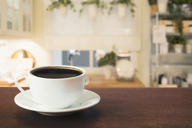 Чашка черного кофе на деревянной столешнице в затуманенное современной кухне или кафе. закройте в помещении. Premium Фотографии