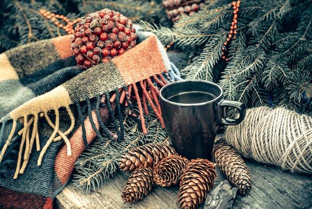 Чашка горячего чая на деревенский деревянный столик. натюрморт из шишек, еловых веток. готовимся к рождеству. Premium Фотографии