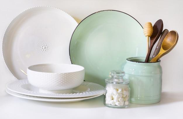 食器、食器、調理器具、その他の白いテーブルトップにある白とターコイズの異なるもの。 Premium写真