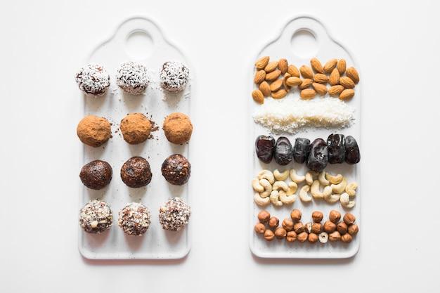 Домодельные шарики энергии с какао и гайками на белизне. Premium Фотографии