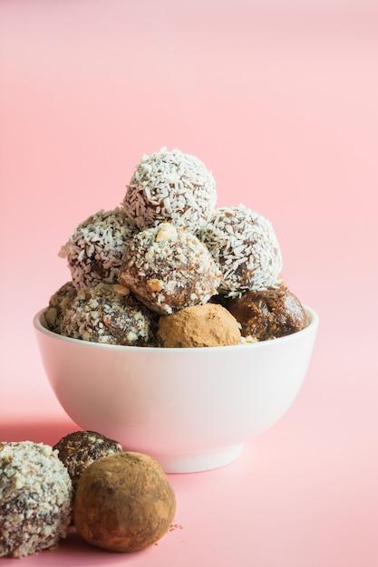 自家製エネルギーボール、カカオ入りビーガンチョコレートトリュフ、ピンクのココナッツ Premium写真