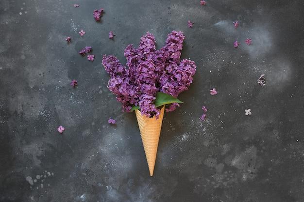 ヴィンテージの黒いテーブルの上のワッフルアイスクリームコーンのピンクのライラックの創造的な静物 Premium写真