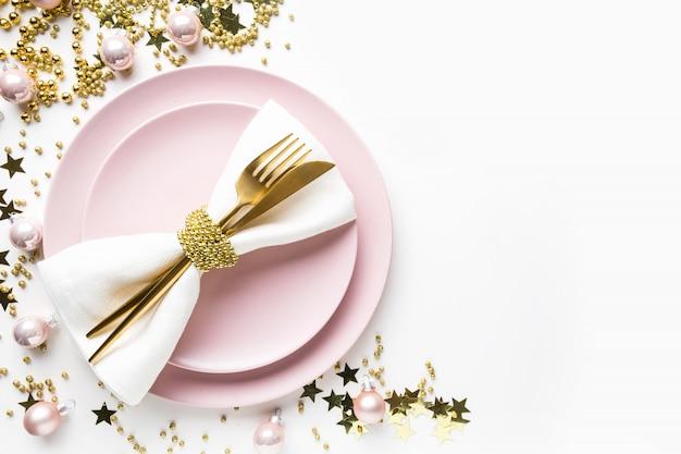 白地にピンクの食器、黄金の銀器でクリスマステーブルの設定。上面図。 Premium写真