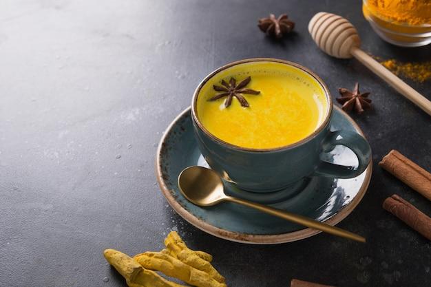 黒のクルクマパウダーとアニススターアーユルヴェーダゴールデンウコンラテミルクのカップ。閉じる。 Premium写真