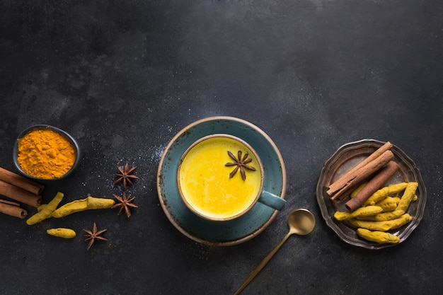 黒のウコンパウダーとアニススターアーユルヴェーダ黄金ウコンミルクのカップ。上からの眺め。 Premium写真