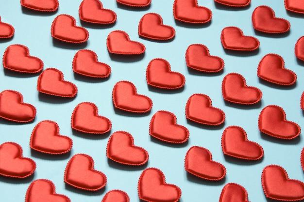 Узор из красных сердец на синем. сердце в изометрическом стиле. валентинка. Premium Фотографии