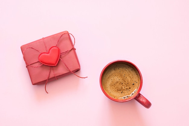 Чашка кофе и подарок с любовью на пастельно-розовый. вид сверху. валентинка. Premium Фотографии