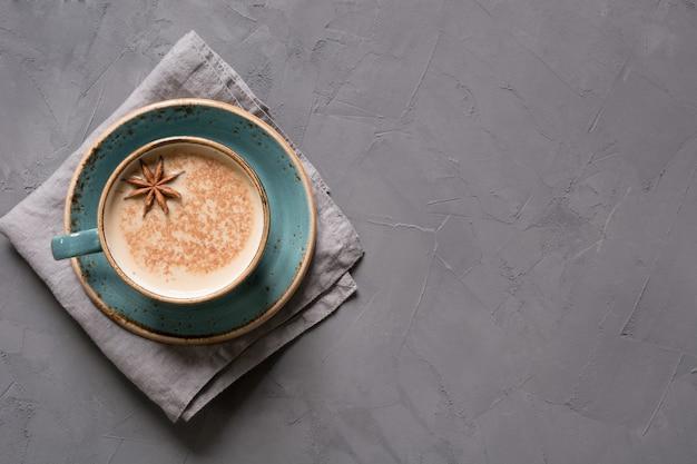 Масала индийский чай или кофе в синей чашке со специями и корицей на черном. вид сверху. Premium Фотографии