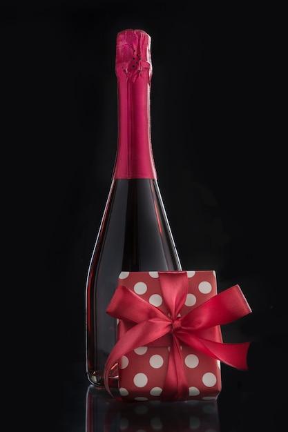 Бутылка розового игристого вина с романтическим подарком и красным бантом. Premium Фотографии