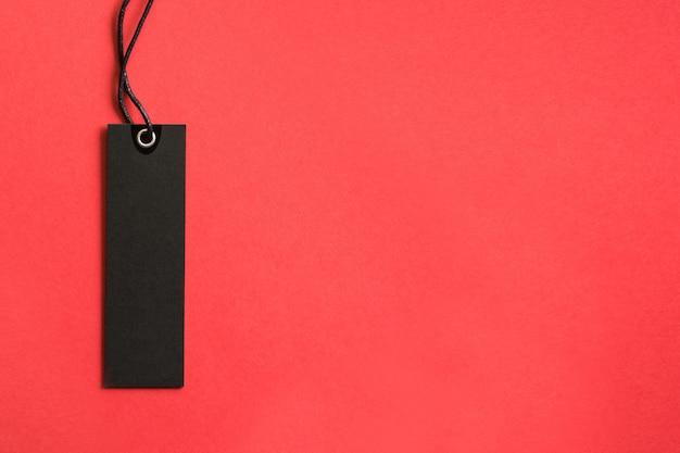 赤い背景に黒い金曜日ショッピングタグ。セール。上からの眺め。 Premium写真