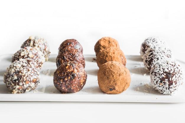 自家製エナジーバイト、カカオとココナッツフレークのビーガンチョコレートトリュフ健康食品のコンセプトです。 Premium写真