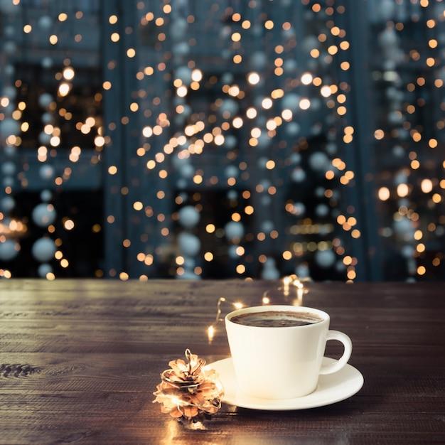 Чашка черного кофе на деревянный стол в кафе. рождественские огни и золотая гирлянда на фоне. Premium Фотографии