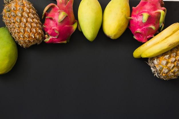 トロピカルフルーツパイナップル、バナナ、ドラゴンフルーツ、黒のマンゴー。上面図。 Premium写真