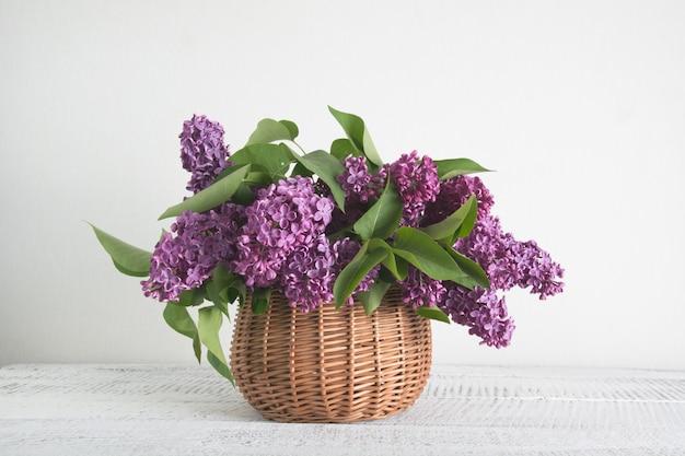 白い木製のテーブルにライラックの花のバスケット Premium写真