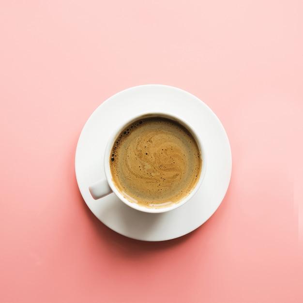 ピンクの表面にブラックコーヒーのカップ Premium写真