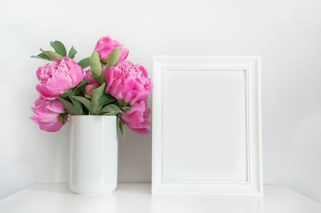 白のテキストのためのフォトフレームと花瓶にピンクの牡丹の花束。母の日。 Premium写真