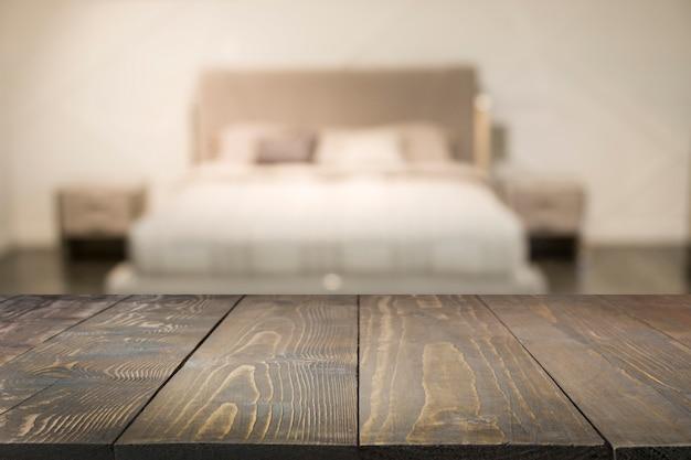Пустая деревянная доска и запачканная современная спальня с интерьером дома как предпосылка. Premium Фотографии