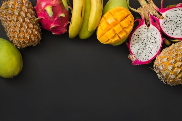 トロピカルフルーツパイナップル、バナナ、ドラゴンフルーツ、ブラックのマンゴー。上面図。 Premium写真