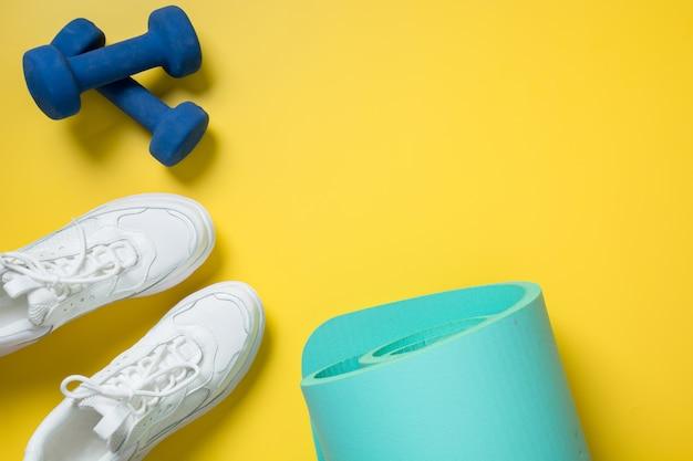 スポーツとフィットネスの靴、ダンベル、黄色のヨガマット。テキスト用のスペース Premium写真