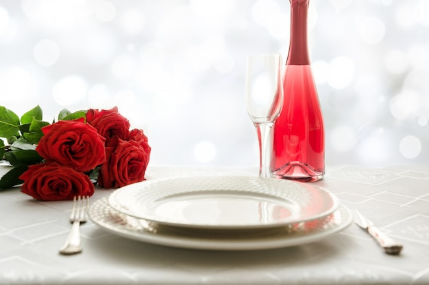 Урегулирование места стола дня святого валентина с красными розами и шампанским. приглашение на свидание. Premium Фотографии